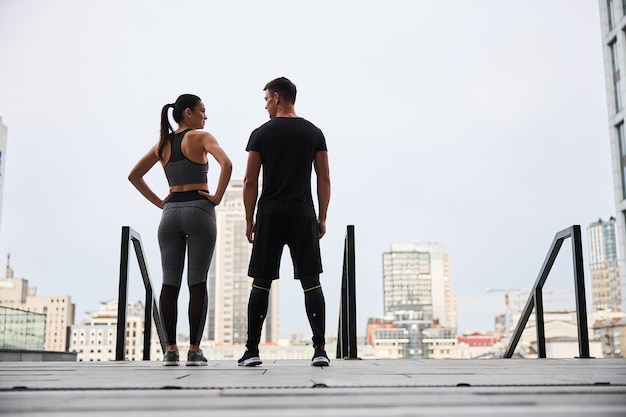 Joyful young slim woman and man are standing together on stairs above urban scenery after training