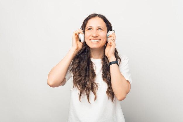うれしそうな若い笑顔の女性は、白い背景の上にワイヤレスイヤホンを試しています。