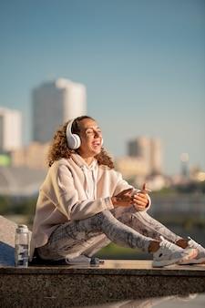 Радостная молодая спортсменка в наушниках смеется, сидя на мраморной плиточной конструкции и слушает радио после тренировки на открытом воздухе