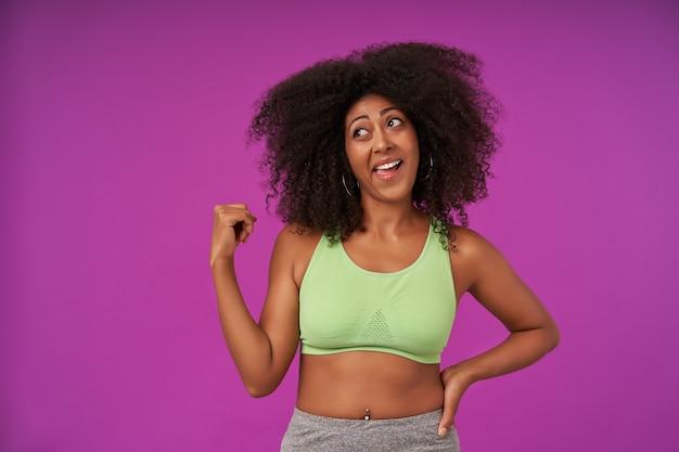 Gioioso giovane sportivo dalla pelle scura femmina con capelli ricci isolato su viola, guardando da parte con viso confuso e alzando la mano, indossando la parte superiore verde chiaro