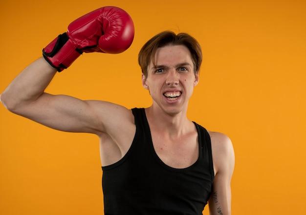 Joyful young sporty guy wearing boxing gloves raising hand isolated on orange wall