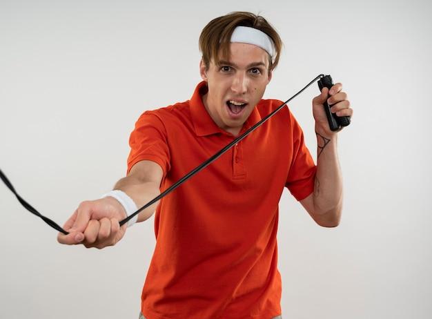 Радостный молодой спортивный парень в повязке на голову с браслетом, растягивающим скакалку