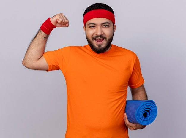 Радостный молодой спортивный мужчина с повязкой на голову и браслетом, держащим коврик для йоги, показывающий сильный жест, изолированный на белом фоне