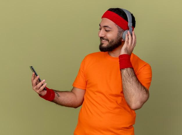 ヘッドバンドとリストバンドを身に着けているうれしそうな若いスポーティな男は、オリーブグリーンの背景で隔離の電話を保持し、見てヘッドフォン
