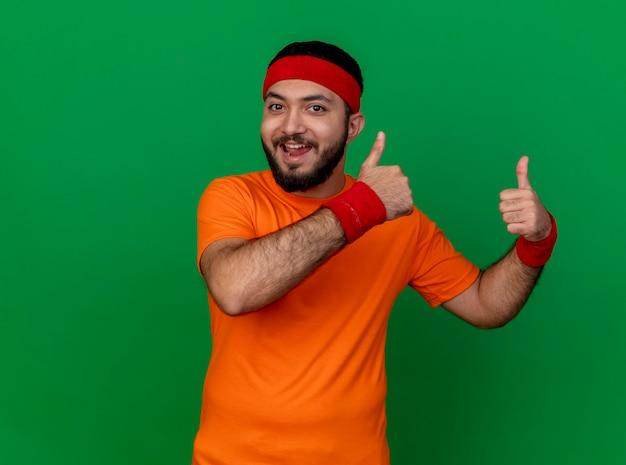 Gioioso giovane uomo sportivo che indossa la fascia e il braccialetto che mostra i pollici in su isolato su sfondo verde con copia spazio