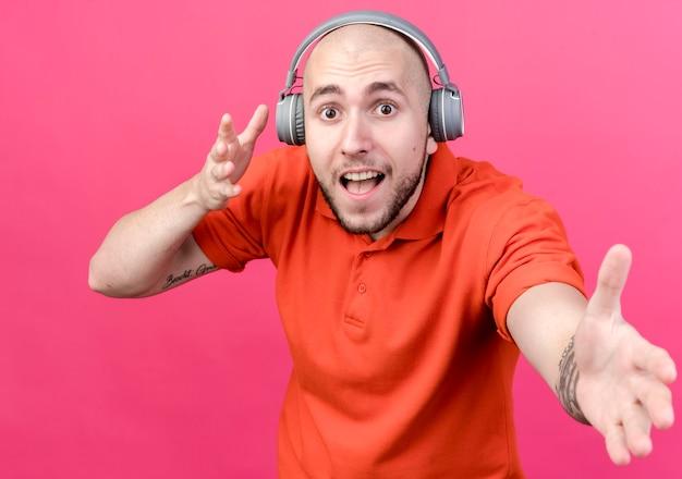 헤드폰을 착용하고 분홍색 벽에 고립 된 손을 잡고 즐거운 젊은 스포티 한 남자