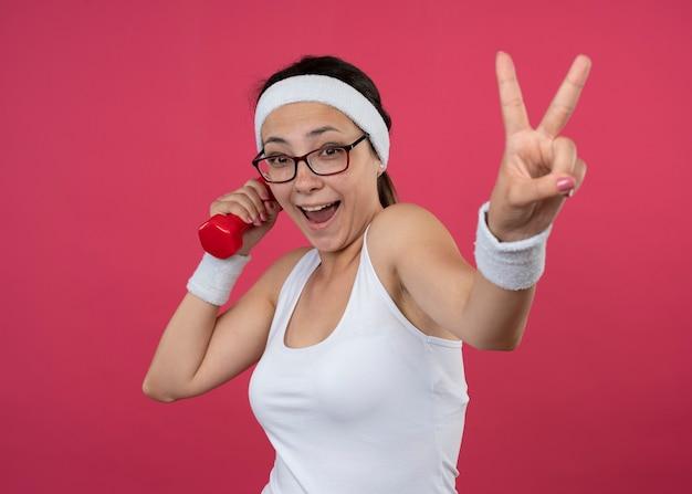 Gioiosa giovane donna sportiva in occhiali ottici che indossa la fascia e braccialetti tiene il segno della mano di vittoria di gesti e manubri isolato sul muro rosa