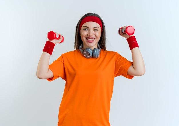 白い壁に分離されたダンベルを上げる首にヘッドバンドとリストバンドとヘッドフォンを身に着けているうれしそうな若いスポーティな女性