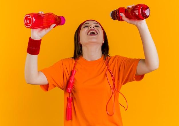 목 주위에 점프 로프와 함께 머리띠와 팔찌를 입고 즐거운 젊은 스포티 한 여자가 물을 마실 준비를하는 병을보고