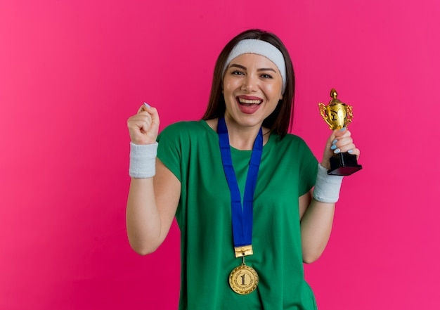 예 제스처를하고 찾고 우승자 컵을 들고 목에 메달과 머리띠와 팔찌를 착용하는 즐거운 젊은 스포티 한 여자