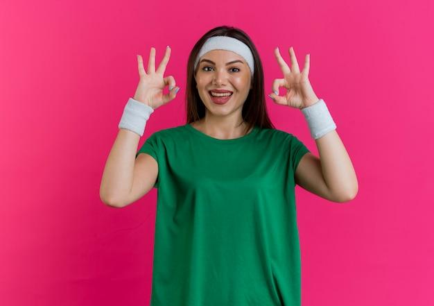 Gioiosa giovane donna sportiva che indossa la fascia e braccialetti cercando di fare segno ok