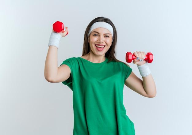 Gioiosa giovane donna sportiva che indossa la fascia e braccialetti cercando di alzare i manubri