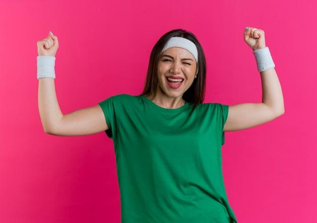 Gioiosa giovane donna sportiva che indossa fascia e braccialetti cercando ammiccanti facendo gesto di sì