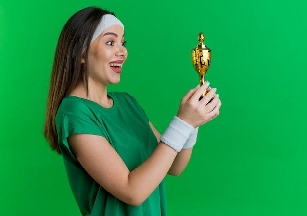Gioiosa giovane donna sportiva che indossa la fascia e braccialetti in piedi in vista di profilo tenendo e guardando la coppa del vincitore
