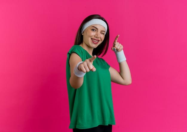 Gioiosa giovane donna sportiva che indossa la fascia e braccialetti in piedi in vista di profilo ammiccanti guardando facendoti gesto