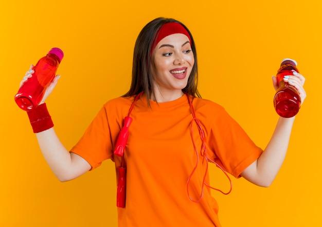 Gioiosa giovane donna sportiva che indossa la fascia e braccialetti con la corda per saltare intorno al collo tenendo guardando le bottiglie d'acqua