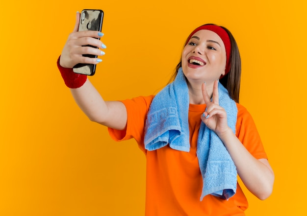 Joyful young sporty woman wearing headband and wristbands with towel around neck doing peace sign taking selfie