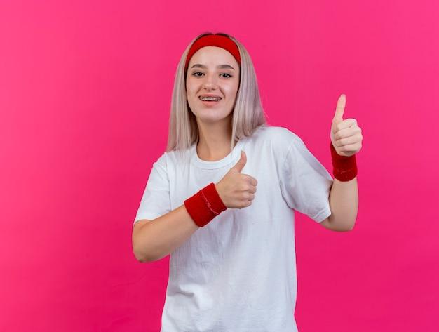Gioiosa giovane donna sportiva con le parentesi graffe che indossa la fascia e braccialetti pollici in su di due mani isolate sulla parete rosa