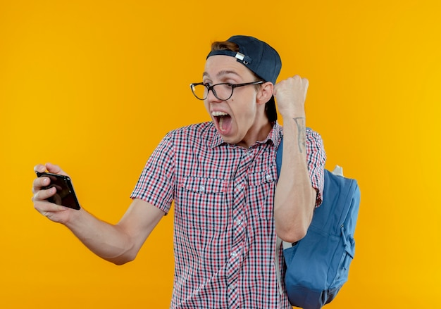 Gioioso giovane studente ragazzo che indossa uno zaino e occhiali e berretto tenendo e guardando il telefono che mostra sì gesto