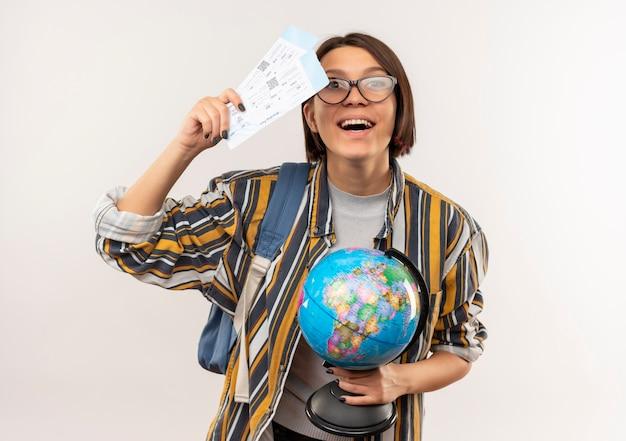 白で隔離の飛行機のチケットと地球儀を保持している眼鏡とバックバッグを身に着けているうれしそうな若い学生の女の子