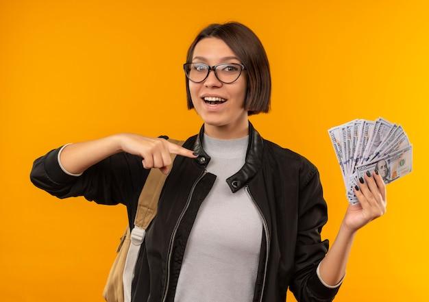 Радостная молодая студентка в очках и задней сумке держит и указывает на деньги, изолированные на оранжевом