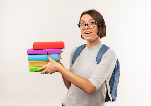 白で隔離の本を保持している眼鏡とバックバッグを身に着けているうれしそうな若い学生の女の子