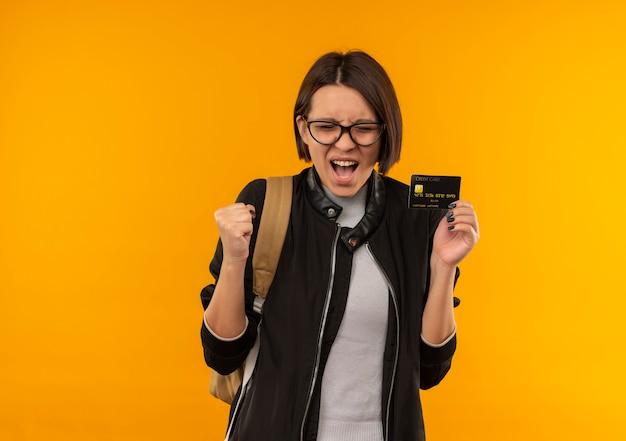 Радостная молодая студентка в очках и задней сумке держит сжимающий кулак кредитной карты с закрытыми глазами, изолированными на оранжевом