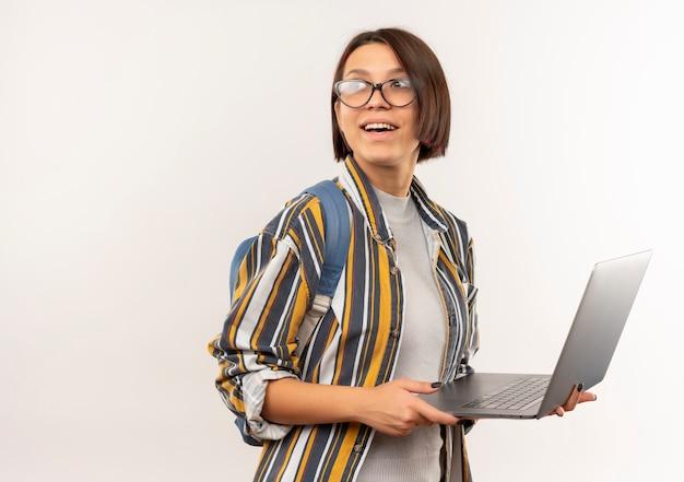 Радостная молодая студентка в очках и задней сумке, держащая ноутбук, глядя на сторону, изолированную на белом