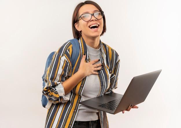 白で隔離の胸に手でラップトップを保持している眼鏡とバックバッグを身に着けているうれしそうな若い学生の女の子