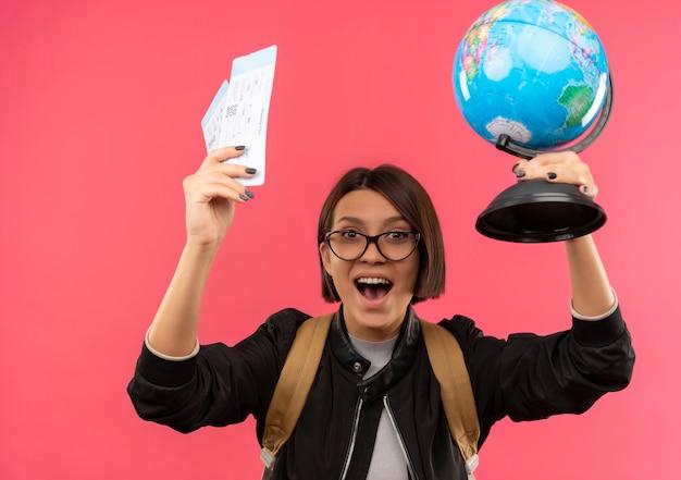 ピンクで隔離の飛行機のチケットと地球儀を上げる眼鏡とバックバッグを身に着けているうれしそうな若い学生の女の子