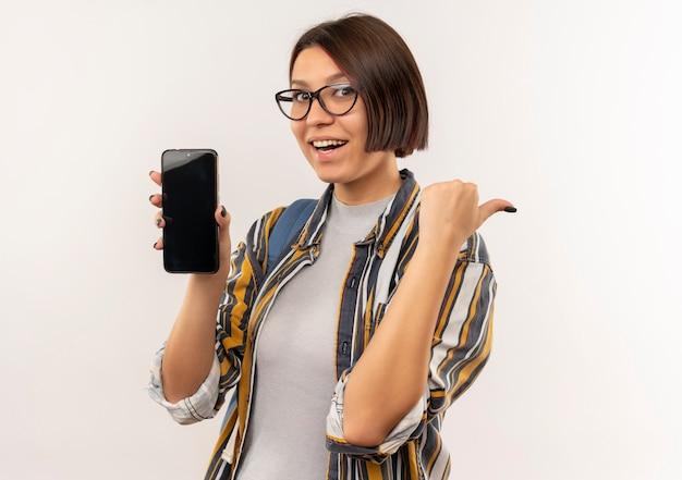 Радостная молодая студентка в очках и задней сумке показывает мобильный телефон, указывающий на сторону, изолированную на белом