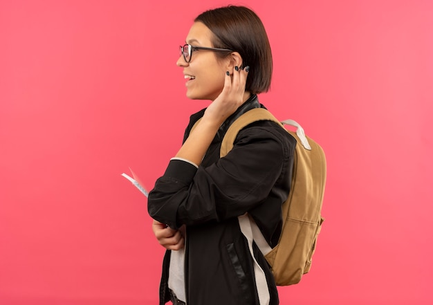 Радостная молодая студентка в очках и задней сумке, стоящая в профиле, держа блокнот и касаясь ее уха, изолированного на розовом