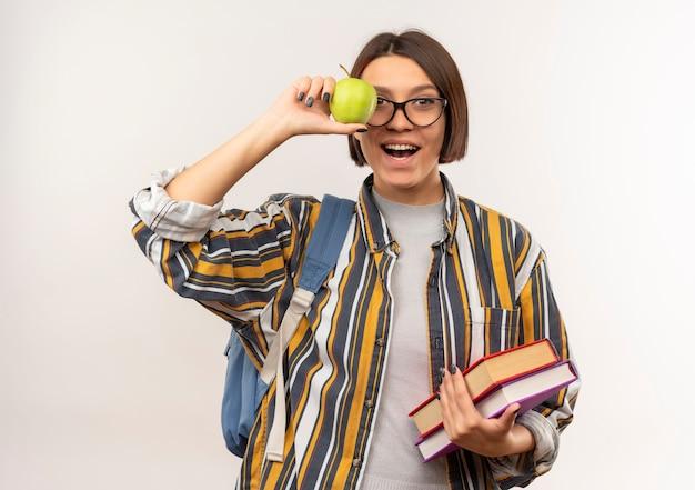 Ragazza allegra giovane studente con gli occhiali e borsa posteriore in possesso di libri e mela isolati su bianco