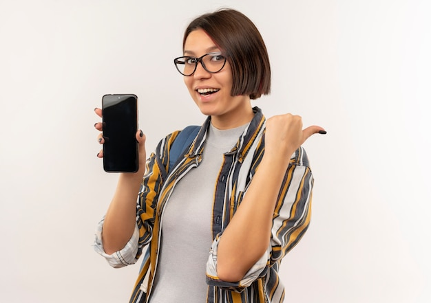Gioiosa ragazza giovane studente con gli occhiali e borsa posteriore che mostra il telefono cellulare che punta sul lato isolato su bianco