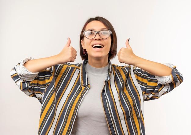Радостная молодая студентка девушка в очках показывает палец вверх, изолированные на белом