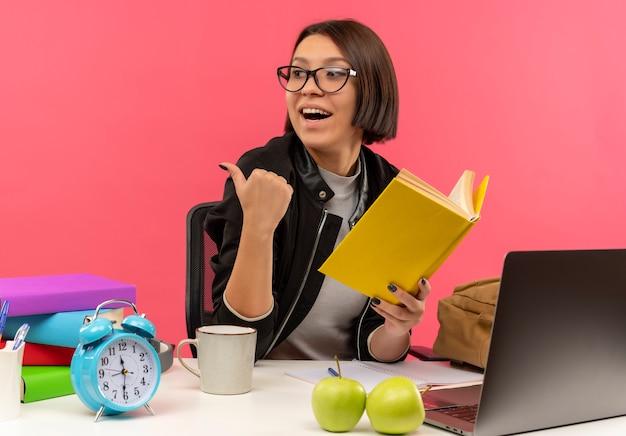 숙제를하고 분홍색에 고립 된 측면을 가리키는 책을 들고 책상에 앉아 안경을 쓰고 즐거운 젊은 학생 소녀