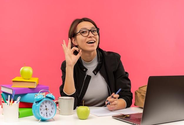 Gioiosa ragazza giovane studente con gli occhiali seduto alla scrivania facendo segno ok isolato sul rosa