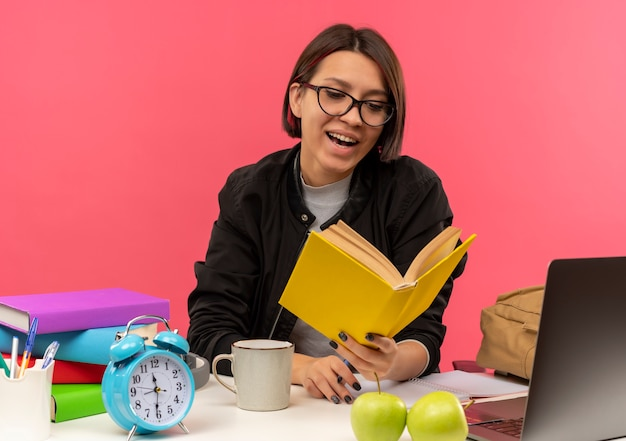 Gioiosa ragazza giovane studente con gli occhiali seduto alla scrivania tenendo e leggendo il libro facendo i compiti isolati sul rosa