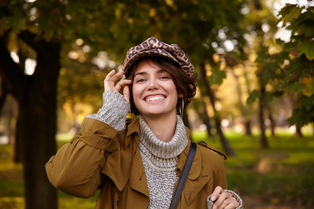 Joyful young stylish short haired brunette lady with natural makeup showing her white perfect teeth while smiling cheerfully, standing over city garden in warm cosy clothes