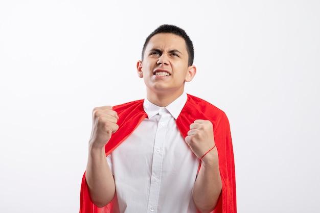 Радостный молодой мальчик-супергерой в красной накидке делает жест да, глядя вверх изолирован на белом фоне с копией пространства