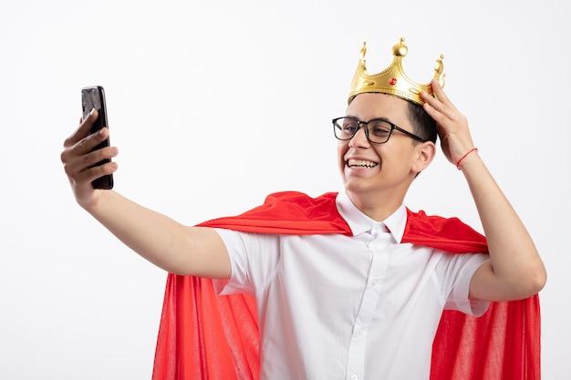 Радостный молодой мальчик-супергерой в красном плаще в очках и трогательной короне с короной, делающий селфи на белом фоне
