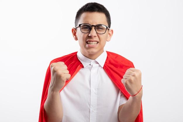 Радостный молодой мальчик-супергерой в красном плаще в очках, глядя в камеру, делает жест да, изолированные на белом фоне