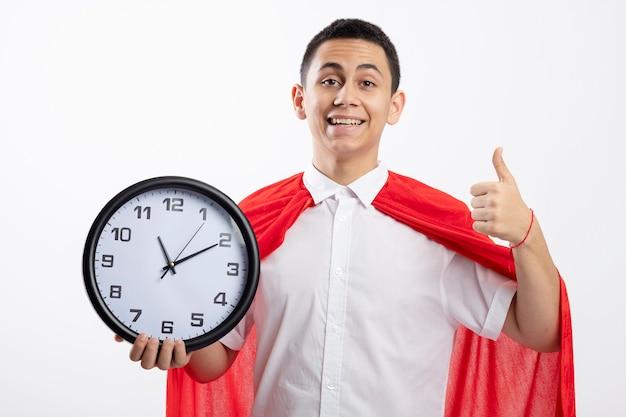 Gioioso giovane supereroe ragazzo in mantello rosso che tiene l'orologio che guarda l'obbiettivo che mostra pollice in su isolato su priorità bassa bianca