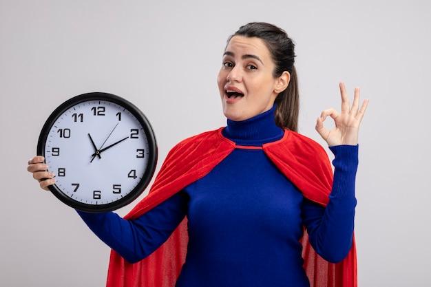 Giovane ragazza allegra del supereroe che tiene l'orologio di parete e che mostra il gesto giusto isolato su bianco