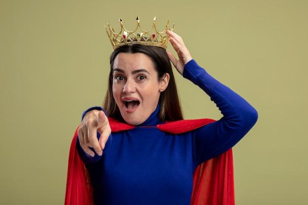 オリーブグリーンに分離されたジェスチャーを示す王冠を身に着けているうれしそうな若いスーパーヒーローの女の子
