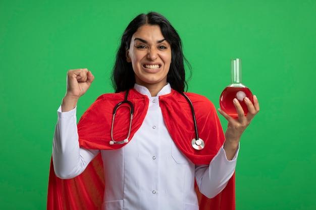 Gioiosa giovane ragazza supereroe che indossa una veste medica con lo stetoscopio che tiene la bottiglia di vetro di chimica riempita di liquido rosso che mostra sì gesto isolato sulla parete verde