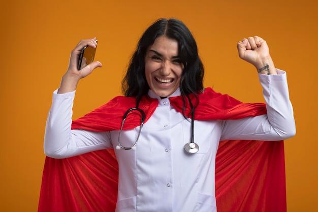 Giovane ragazza allegra del supereroe che indossa la veste medica con lo stetoscopio che tiene il telefono che mostra sì gesto isolato sulla parete arancione