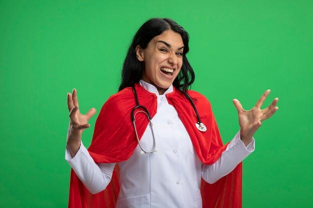 Gioiosa giovane ragazza del supereroe che indossa abito medico con lo stetoscopio diffondendo le mani isolate su verde