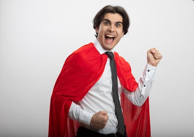 ネクタイを身に着けているカメラを見てうれしそうな若いスーパーヒーローの男は、白で隔離されたはいジェスチャーを示しています