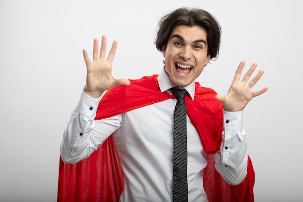 白で隔離の手を広げてネクタイを身に着けているカメラを見てうれしそうな若いスーパーヒーローの男